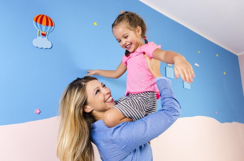 Εκστατική, ευτυχής μητέρα και παιχνίδι κορών στοκ εικόνα
