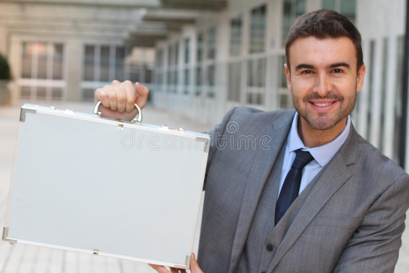 Εκστατικός επιχειρηματίας που κρατά έναν χαρτοφύλακα στοκ εικόνες