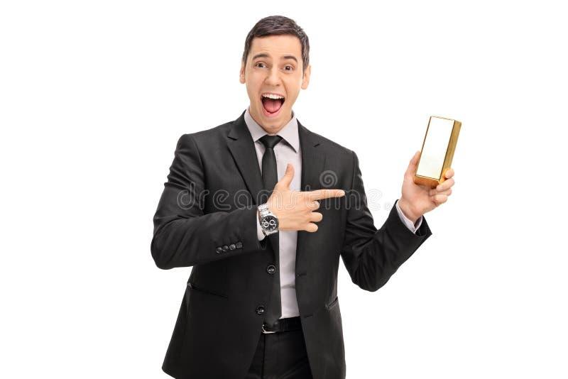 Εκστατικός επιχειρηματίας που κρατά έναν χρυσό φραγμό στοκ φωτογραφία με δικαίωμα ελεύθερης χρήσης