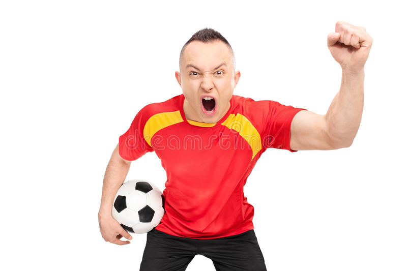 Εκστατικός οπαδός ποδοσφαίρου που κρατά ένα ποδόσφαιρο και ενθαρρυντικός στοκ εικόνα με δικαίωμα ελεύθερης χρήσης