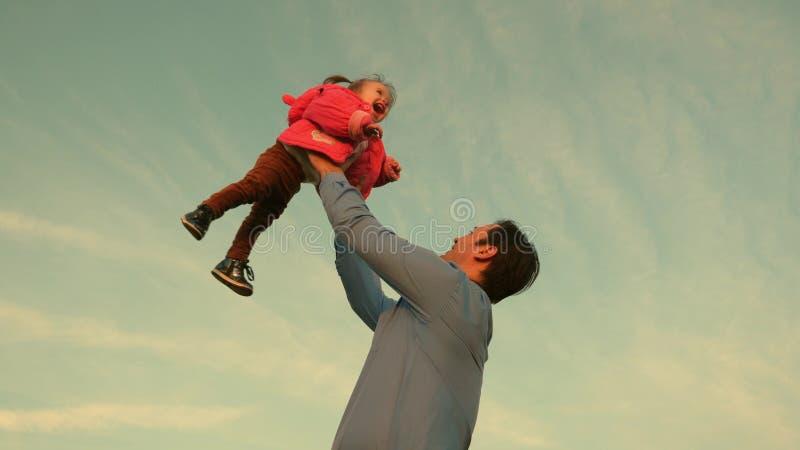 Εκτίναξη μπαμπάδων επάνω ένα παιδί skyward ο πατέρας έριξε το μωρό στον ουρανό οικογένεια έννοιας ευτ& Παιχνίδια μπαμπάδων με το  στοκ εικόνες με δικαίωμα ελεύθερης χρήσης