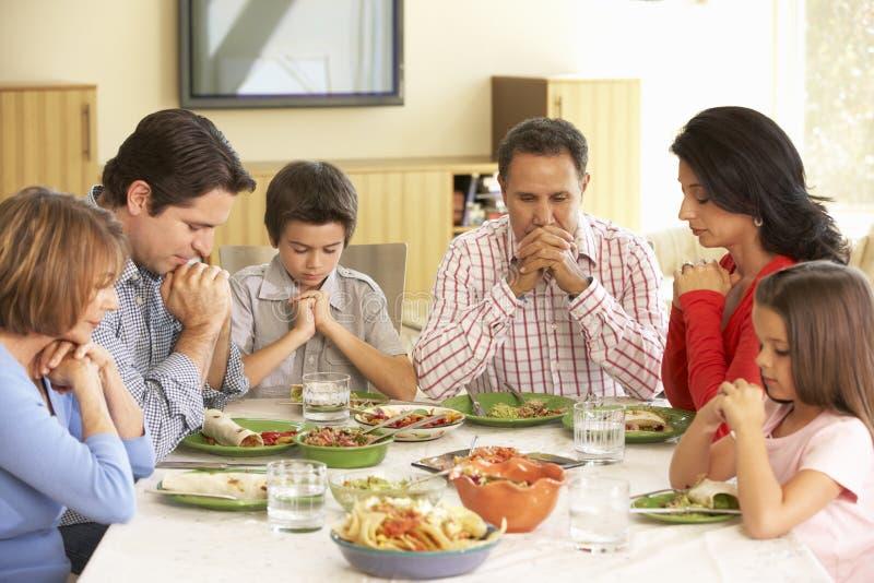 Εκτεταμένη ισπανική οικογένεια που λέει τις προσευχές πριν από το γεύμα στο σπίτι στοκ εικόνες