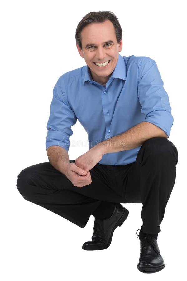 Εκτελεστικό σκύψιμο. Εύθυμη ώριμη συνεδρίαση επιχειρηματιών crouche στοκ εικόνα με δικαίωμα ελεύθερης χρήσης