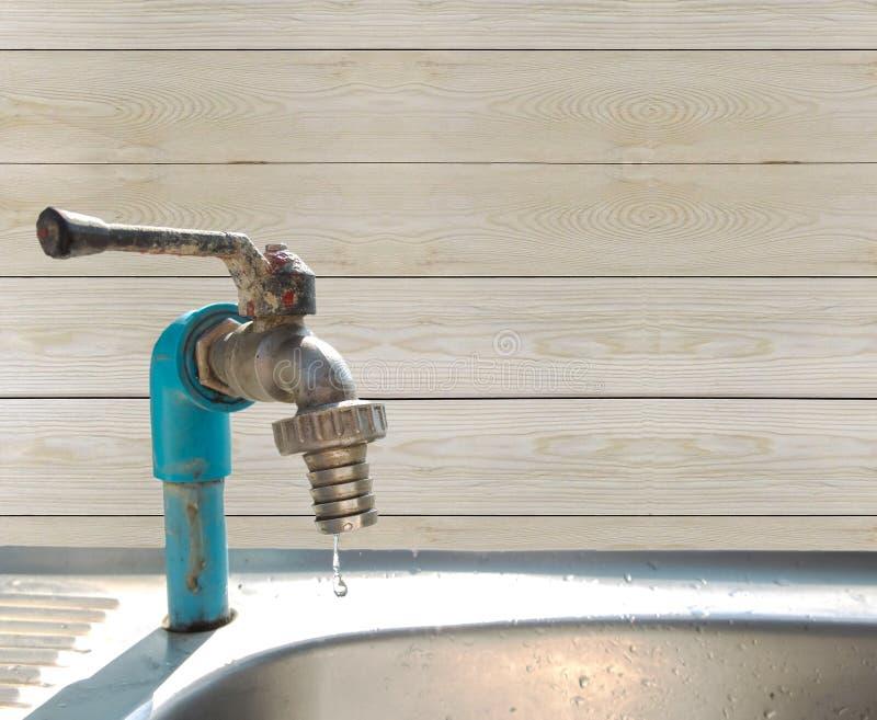 Εκτός από το νερό εκτός από την παγκόσμια έννοια, πτώση νερού από την ελαττωματική στρόφιγγα στη γωνία με το ανοικτό καφέ ξύλινο  στοκ εικόνα
