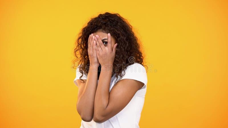 Εκφοβισμένη biracial ταινία τρόμου προσοχής γυναικών, κλείνοντας πρόσωπο με τα χέρια, φόβος στοκ εικόνα