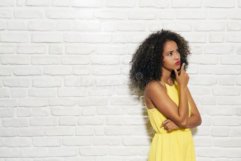 Εκφράσεις του προσώπου της νέας μαύρης γυναίκας στο τουβλότοιχο στοκ εικόνα με δικαίωμα ελεύθερης χρήσης