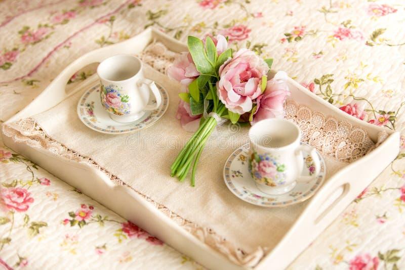 Εκλεκτής ποιότητας δίσκος με τα λουλούδια και τις φλυτζάνες τσαγιού που βρίσκονται στο κρεβάτι στοκ φωτογραφία με δικαίωμα ελεύθερης χρήσης