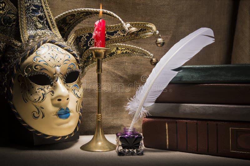 Εκλεκτής ποιότητας ακόμα ζωή με τα παλαιά βιβλία inkstand πλησίον, το φτερό, τη venezian μάσκα και το καίγοντας κόκκινο κερί στο  στοκ εικόνα