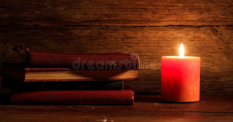 Εκλεκτής ποιότητας βιβλία και ένα κερί στο ξύλινο υπόβαθρο στοκ εικόνα
