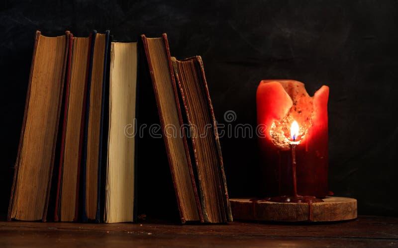 Εκλεκτής ποιότητας βιβλία και κερί στο σκοτεινό υπόβαθρο στοκ φωτογραφίες