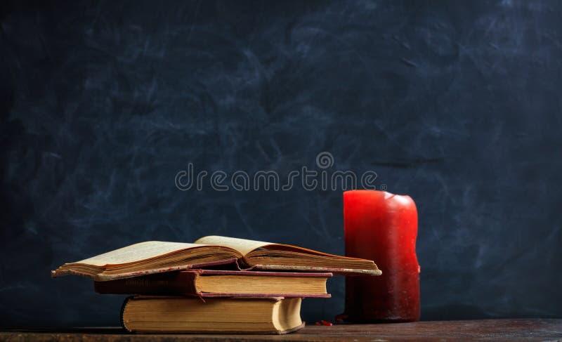 Εκλεκτής ποιότητας βιβλία και κερί στο υπόβαθρο πινάκων στοκ φωτογραφία με δικαίωμα ελεύθερης χρήσης