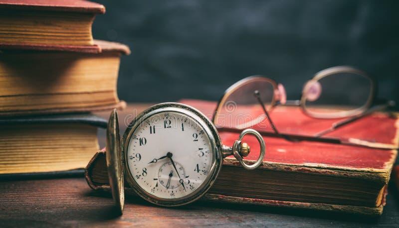 Εκλεκτής ποιότητας βιβλία και ρολόι τσεπών στο σκοτεινό υπόβαθρο στοκ εικόνες
