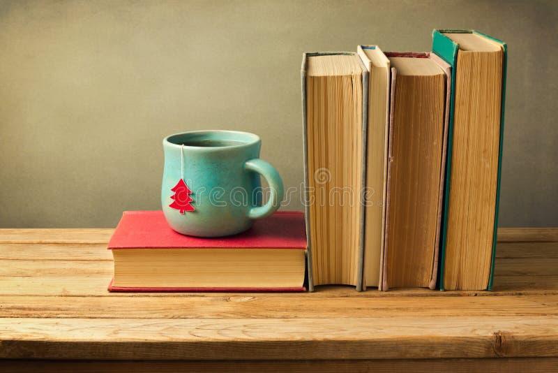 Εκλεκτής ποιότητας βιβλία και φλυτζάνι τσαγιού στον ξύλινο πίνακα γιορτάστε τη φθορά santa μητέρων καπέλων κορών Χριστουγέννων εο στοκ φωτογραφία