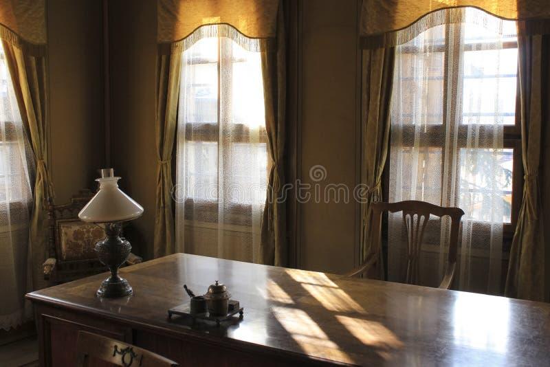Εκλεκτής ποιότητας γραφείο - ξύλινος πίνακας εργασίας και μεγάλα παράθυρα στοκ φωτογραφία