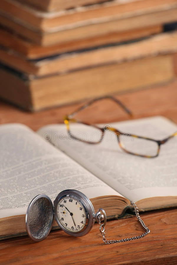 Εκλεκτής ποιότητας γυαλιά ρολογιών τσεπών και ανοικτό παλαιό βιβλίο στοκ φωτογραφία