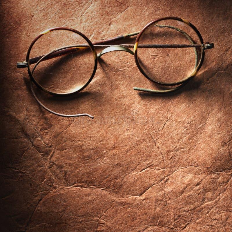 Εκλεκτής ποιότητας γυαλιά σε παλαιό χαρτί στοκ εικόνες