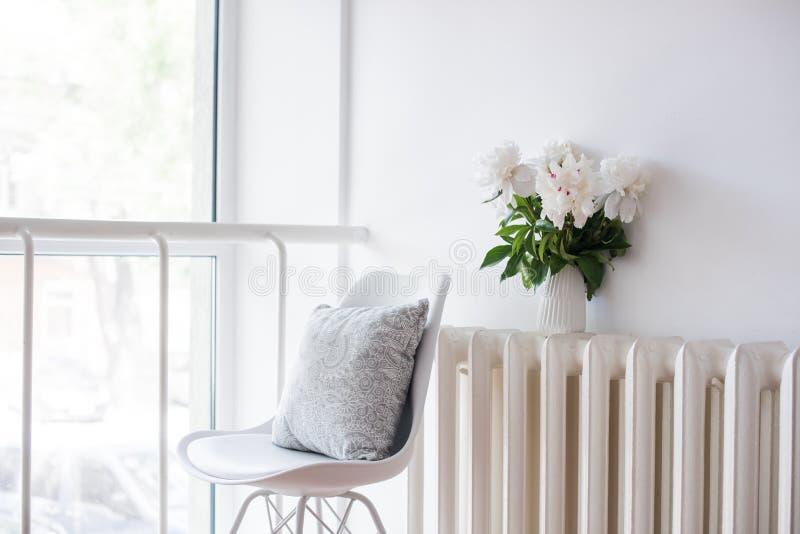 Εκλεκτής ποιότητας εγχώρια διακόσμηση, φρέσκες peonies και καρέκλα σχεδιαστών με στοκ εικόνα