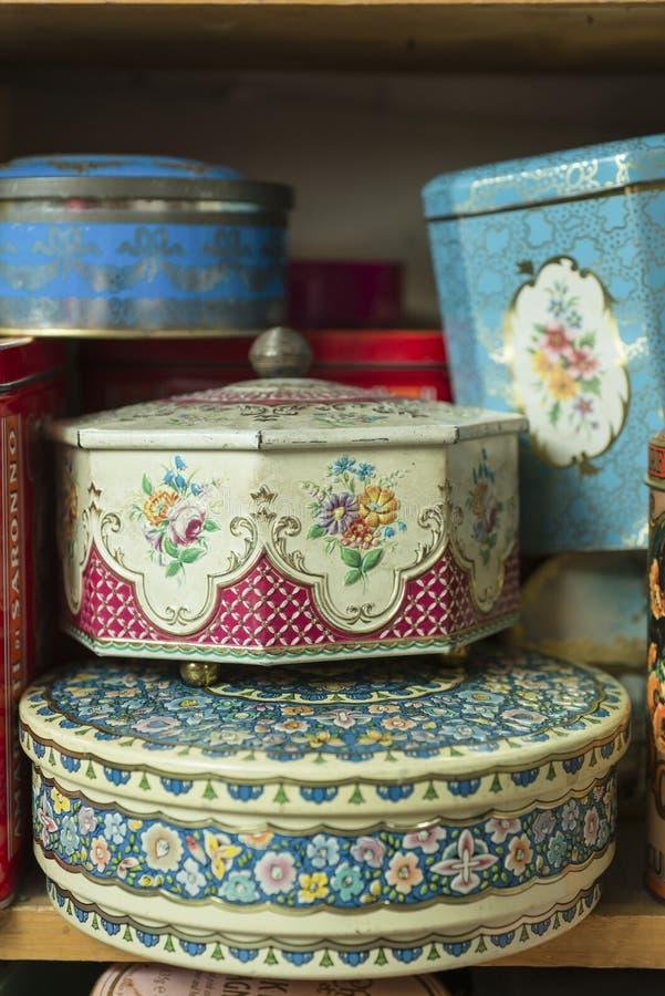 Εκλεκτής ποιότητας διακοσμητικά μεταλλικά κουτιά κασσίτερου στο ξύλινο ράφι στοκ φωτογραφία με δικαίωμα ελεύθερης χρήσης