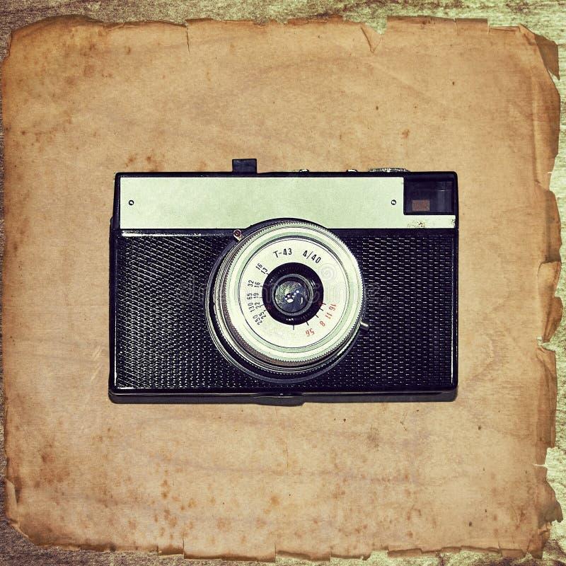 Εκλεκτής ποιότητας κάμερα σε παλαιό χαρτί grunge στοκ εικόνες