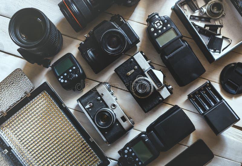Εκλεκτής ποιότητας κάμερα ταινιών, ψηφιακή κάμερα DSLR και εξαρτήματα στην άσπρη ξύλινη έννοια ανάπτυξης τεχνολογίας υποβάθρου Το στοκ εικόνα με δικαίωμα ελεύθερης χρήσης