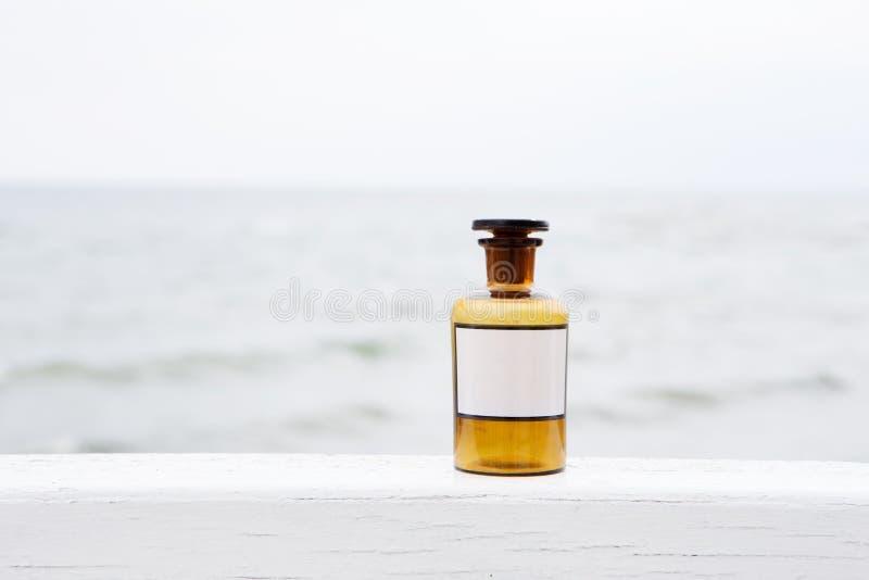 Εκλεκτής ποιότητας μπουκάλι ιατρικής στο υπόβαθρο θάλασσας στοκ εικόνα με δικαίωμα ελεύθερης χρήσης