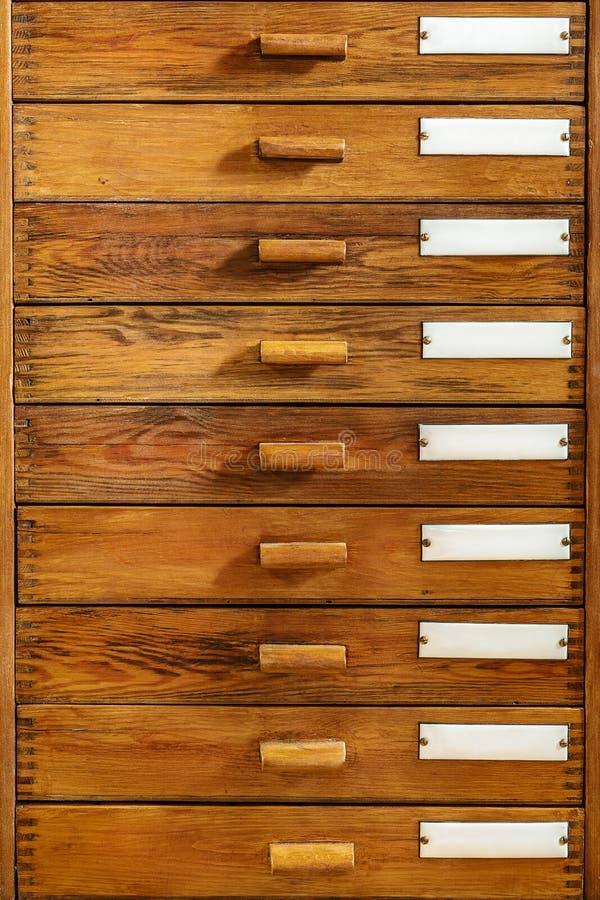 Εκλεκτής ποιότητας ξύλινα συρτάρια με τις κενές ετικέτες σμάλτων στοκ φωτογραφίες
