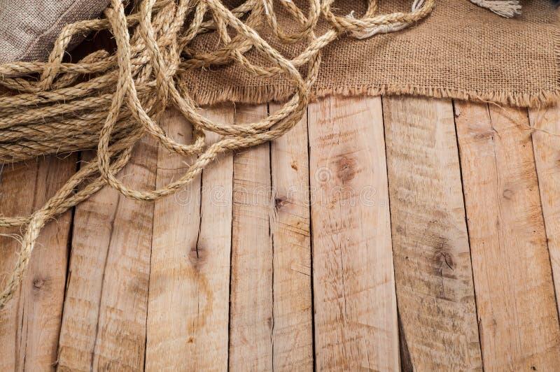 Εκλεκτής ποιότητας πίνακας εργασίας με το σχοινί, burlap σάκος στην ξύλινη επιφάνεια σανίδων στοκ εικόνα