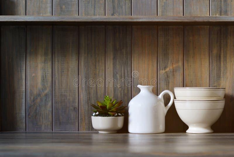 Εκλεκτής ποιότητας πιατικά και μικρές εγκαταστάσεις σε ένα σκοτεινό ξύλινο υπόβαθρο στοκ εικόνες