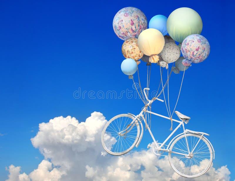 Εκλεκτής ποιότητας ποδήλατο που πετά επάνω στον ουρανό με τα μπαλόνια στοκ φωτογραφία