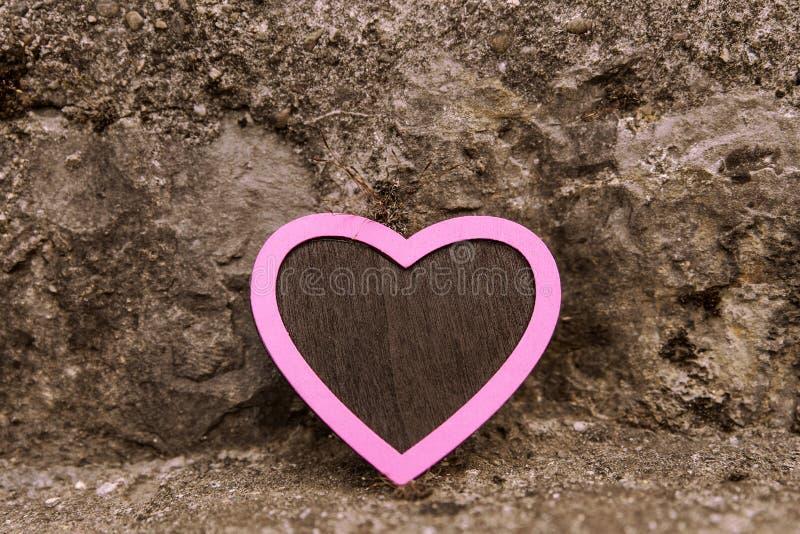 Εκλεκτής ποιότητας ρόδινη καρδιά μπροστά από ένα πετρώδες υπόβαθρο στοκ φωτογραφίες