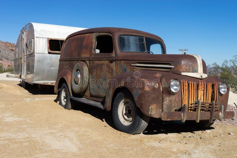 Εκλεκτής ποιότητας σκουριασμένα αυτοκίνητο και ρυμουλκό στην έρημο στοκ φωτογραφίες