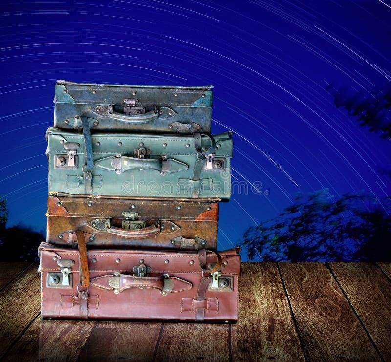 Εκλεκτής ποιότητας τσάντα ταξιδιού στο ξύλινο tabel με τις αστέρι-ουρές στο υπόβαθρο νυχτερινού ουρανού στοκ εικόνες