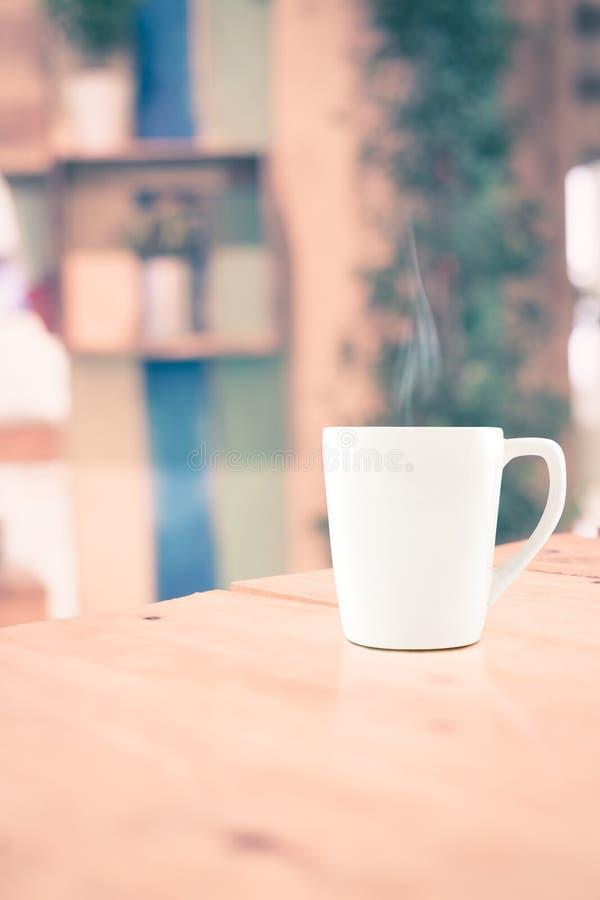 Εκλεκτής ποιότητας φίλτρο: Άσπρο φλυτζάνι καφέ στον ξύλινο πίνακα στην ΤΣΕ καφέδων θαμπάδων στοκ φωτογραφία με δικαίωμα ελεύθερης χρήσης