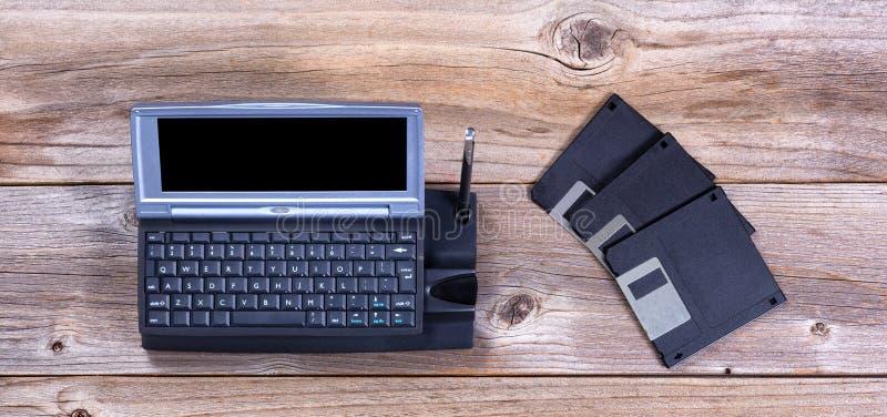 Εκλεκτής ποιότητας φορητοί δίσκοι υπολογιστών και στοιχείων στους αγροτικούς ξύλινους πίνακες στοκ εικόνες