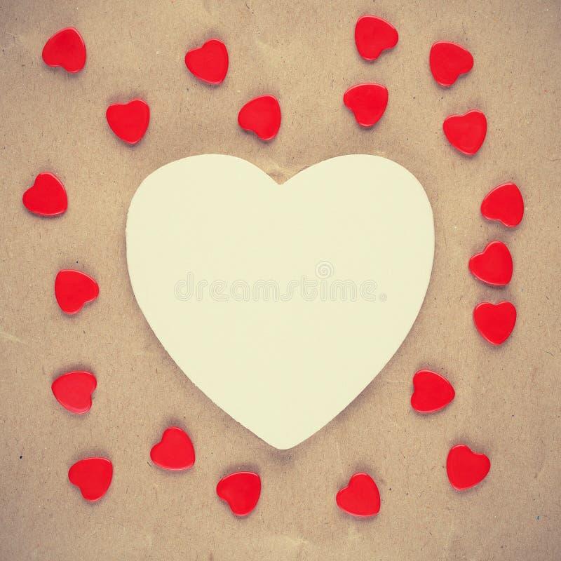 Εκλεκτής ποιότητας φωτογραφία της άσπρης καρδιάς και των μικρών κόκκινων καρδιών στοκ εικόνες