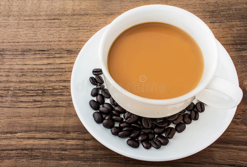Εκλεκτής ποιότητας φλυτζάνι και φασόλια καφέ στο ξύλινο υπόβαθρο grunge στοκ φωτογραφία με δικαίωμα ελεύθερης χρήσης