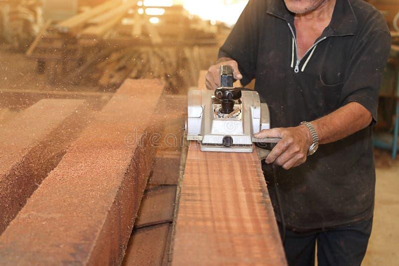 Εκλεκτικός στην ηλεκτρική μηχανή πλανίσματος συνεργάζεται με τον ανώτερο ξυλουργό στο εργαστήριο ξυλουργικής πεδίο βάθους ρηχό στοκ εικόνα