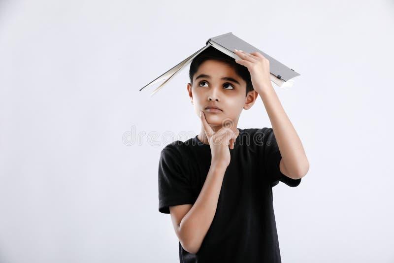 ελάχιστα ινδικό/ασιατικό αγόρι με το βιβλίο σε επικεφαλής και να σκεφτεί σοβαρά στοκ φωτογραφίες