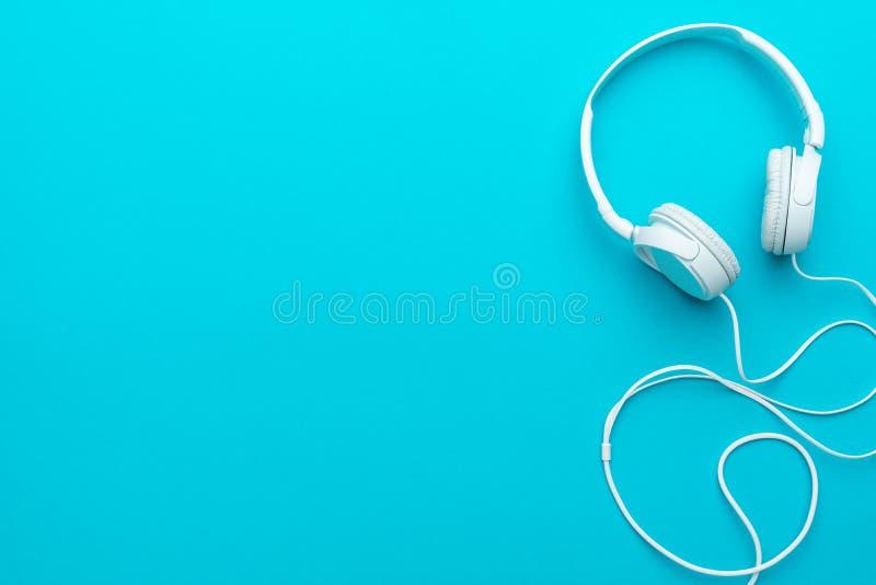Ελάχιστη φωτογραφία των άσπρων ακουστικών με το καλώδιο στο μπλε υπόβαθρο με το διάστημα αντιγράφων στοκ φωτογραφίες με δικαίωμα ελεύθερης χρήσης