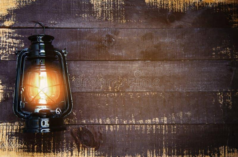 Ελαιολυχνία τη νύχτα σε έναν ξύλινο τοίχο - ο παλαιός εκλεκτής ποιότητας κλασικός Μαύρος φαναριών στοκ εικόνα