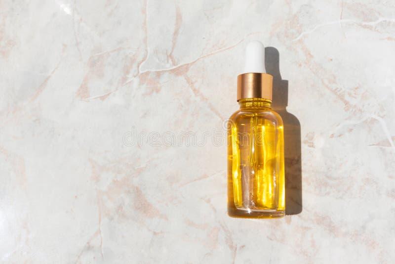Ελαιούχος ορός στο μπουκάλι γυαλιού με το σιφώνιο στο μαρμάρινο υπόβαθρο με το διάστημα αντιγράφων στοκ εικόνα με δικαίωμα ελεύθερης χρήσης