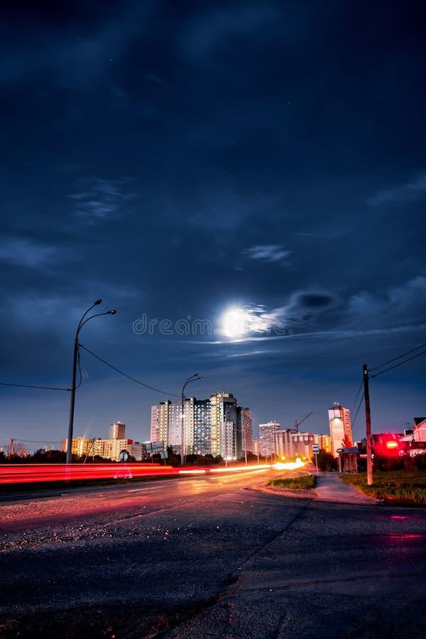 Ελαφριά ίχνη αυτοκινήτων μπροστά από τα απόμακρα στο κέντρο της πόλης κτήρια στη θερινή νύχτα στοκ εικόνες