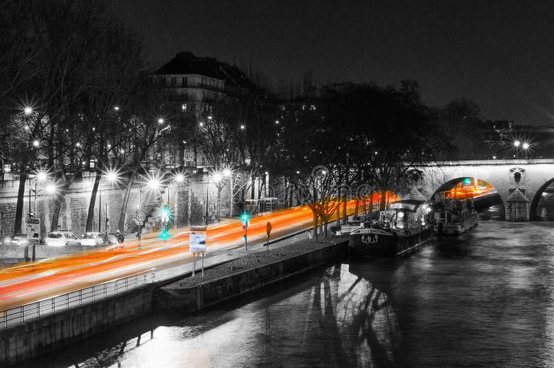 Ελαφριά ίχνη αυτοκινήτων στην αποβάθρα του Παρισιού τη νύχτα, μακριά φωτογραφία έκθεσης από το Σηκουάνα στοκ εικόνα με δικαίωμα ελεύθερης χρήσης