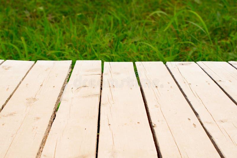 Ελαφρύς ξύλινος πίνακας σε ένα υπόβαθρο της πράσινης χλόης στοκ φωτογραφίες με δικαίωμα ελεύθερης χρήσης