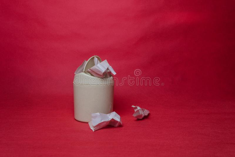 Ελαφρύ δοχείο απορριμμάτων στο κόκκινο υπόβαθρο Κινηματογράφηση σε πρώτο πλάνο των τσαλακωμένων φύλλων του εγγράφου Έννοια των πε στοκ φωτογραφία με δικαίωμα ελεύθερης χρήσης