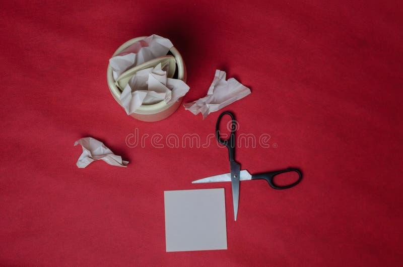 Ελαφρύ δοχείο απορριμμάτων στο κόκκινο υπόβαθρο Κινηματογράφηση σε πρώτο πλάνο των τσαλακωμένων φύλλων του εγγράφου και του ψαλιδ στοκ εικόνες με δικαίωμα ελεύθερης χρήσης