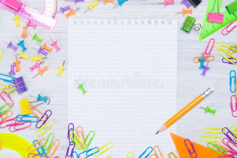 Ελαφρύ ξύλινο υπόβαθρο με τα χρωματισμένα μολύβια στις πλευρές του ψαλιδισμένου σημειωματάριου, υπάρχει μια θέση για το γράψιμο σ στοκ εικόνα
