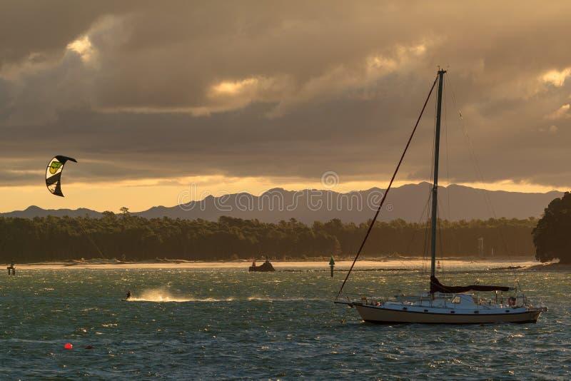 Ελαφρύ σπάσιμο ηλιοβασιλέματος μέσω των θυελλωδών σύννεφων πέρα από τον κόλπο στοκ εικόνες
