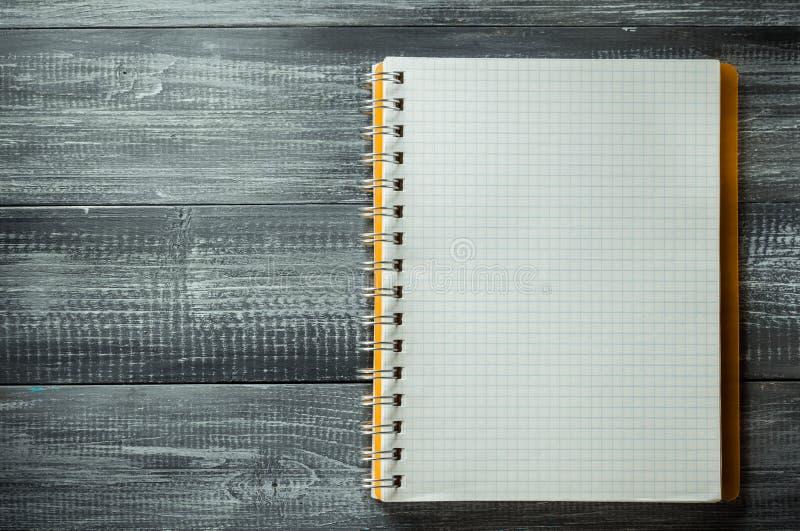 ελεγχμένο σημειωματάριο στον ξύλινο πίνακα στοκ φωτογραφίες