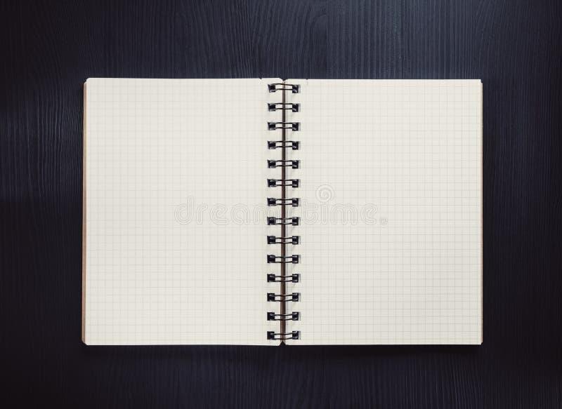 ελεγχμένο σημειωματάριο στο μαύρο ξύλο στοκ εικόνες